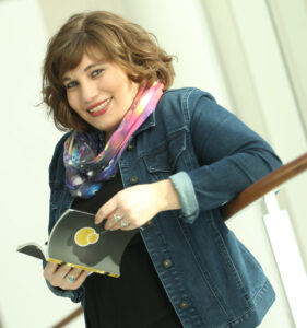 Marlena Chertock, a white writer with short brown hair in a jean jacket with a space scarf holding a copy of her book.