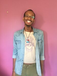 Malik, a queer Black man, in front of a purple wall.